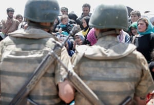 Syrian refugees waiting on the Syrian side of the border crossing near Akçakale