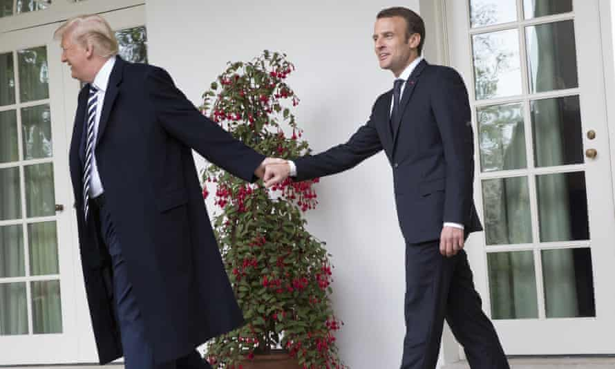 Donald Trump leads Emmanuel Macron by the hand.