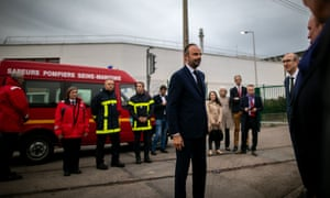 The French prime minister, Edouard Philippe, walks past firefighters at the Lubrizol chemical factory in Rouen