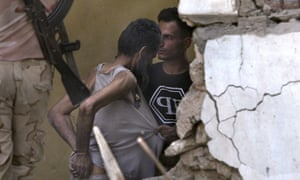 A suspected Isis fighter is led away after surrendering to Iraqi army soldiers on 18 July amid the ruins of the Old City.