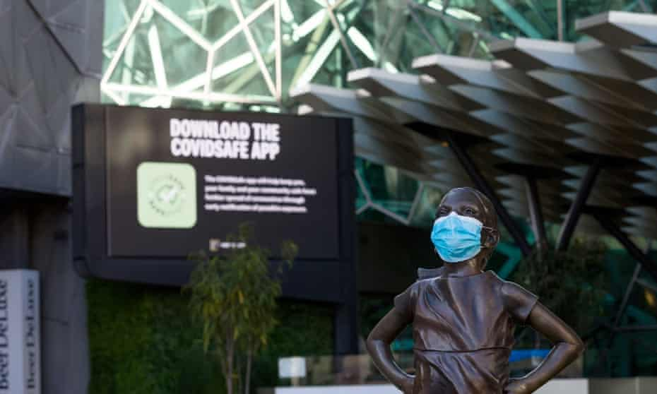 """The """"Fearless Girl' statue wears a mask in Federation Square in Melbourne."""
