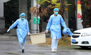 Staff carry a box at Jinyintan hospital in Wuhan, where the fourth fatality of the viral outbreak was reported on Tuesday.