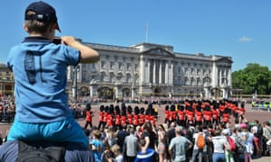 Tourists watch the changing of the guard at Buckingham Palace in London
