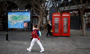 Women walk past red telephone boxes in the centre of Gibraltar.