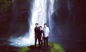 The xx in Iceland. The band are pictured in front of a cascading waterfall while stood on a mossy bank.