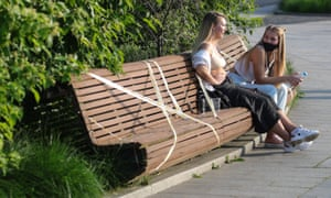 Young women sit on a taped off bench in Moscow.