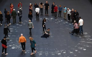 London, UK: The artist Tania Bruguera, centre, and guests create her artwork on a heat-sensitive floor during the unveiling of the installation at the Turbine Hall in the Tate Modern