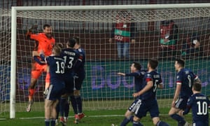 Scotland players rush to celebrated with keeper David Marshall after saving the penalty of Serbia's Aleksandar Mitrovic to win the penalty shoot out and qualify for the Euro2020 finals.