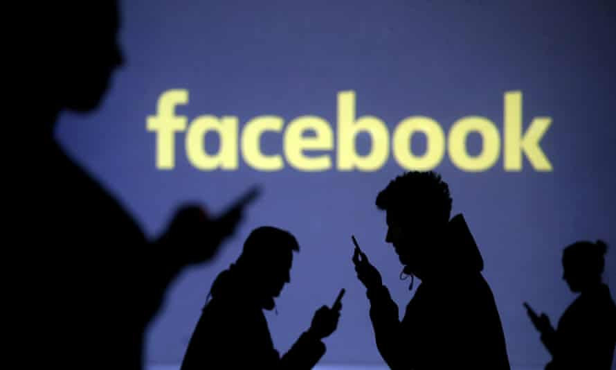 Silhouettes of mobile phone users are seen next to a screen projection of the Facebook logo