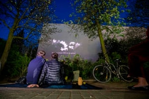Residents watch the movie Loving Vincent projected on the wall of a neighbouring building from their front garden