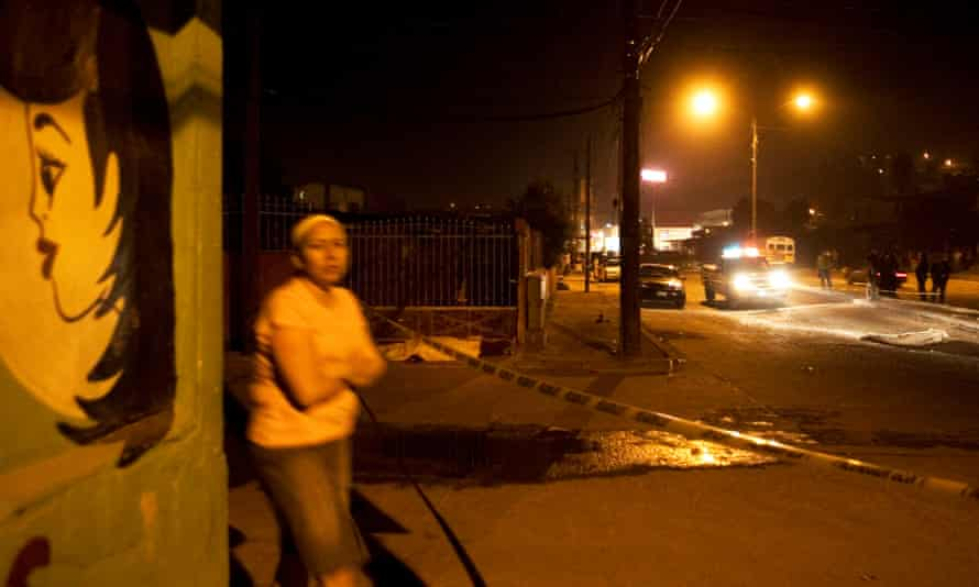 A woman walks past two men dead in a road after a shootout in Tijuana, Mexico, on 17 November 2008.