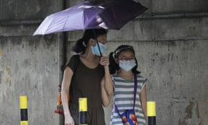 People wear masks as they pass by a Chinese-Filipino school in Manila that suspended classes as a precautionary measure against the virus on Monday.