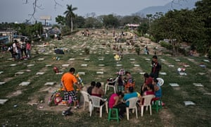 Families seated on plastic chairs at the general cemetery