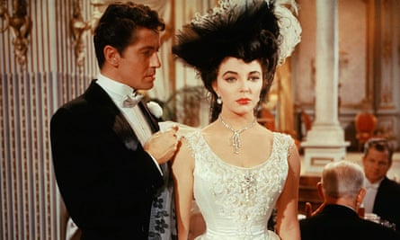 Joan Collins in an elaborate hat and lacy white dress with Farley Granger in The Girl in the Red Velvet Swing, 1955.