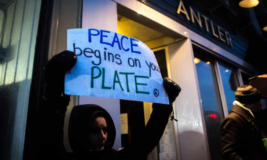 Vegan protesters gather outside of the Antler restaurant in Toronto.