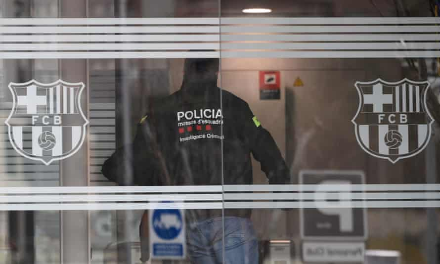 A policeman enters the Camp Nou offices.
