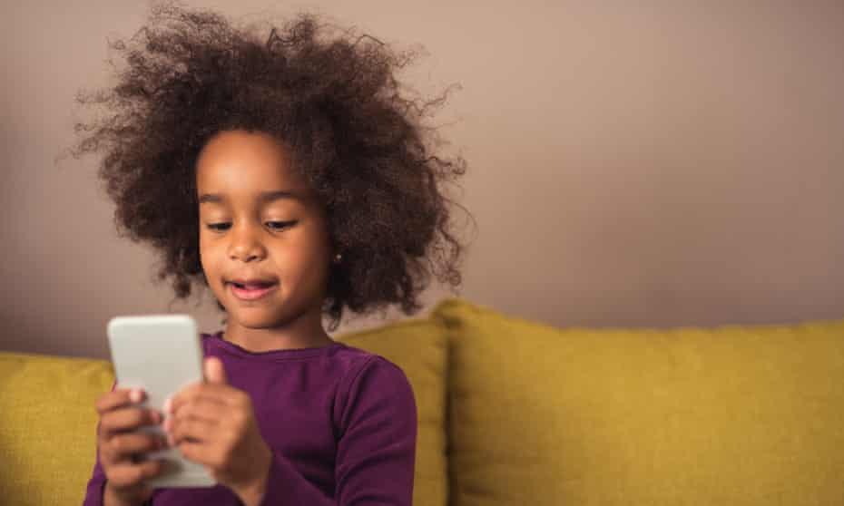 a young girl looking at a mobile phone