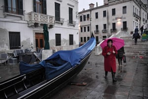 "A resident walks past a gondola stranded on Riva degli Schiavoni, after being washed away during an exceptional overnight ""Alta Acqua"" high tide water level"