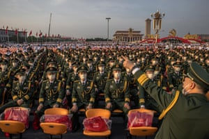 Chinese military members wait in Tiananmen Square before a parade marking the anniversary