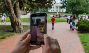 A woman holds up her cell phone as she plays the Pokemon Go game in Lafayette Park in front of the White House