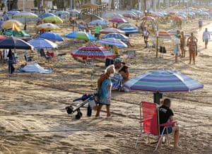 Torrevieja, Spain. A woman looks for a free space on Cura beach which has been divided into sections to keep beachgoers at a safe distance from each other