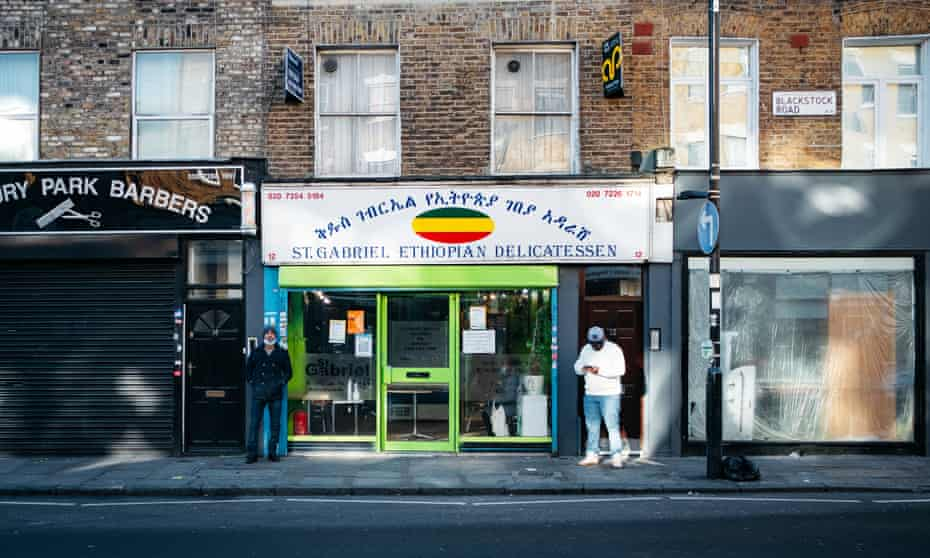مشتریان در مقابل خیابان گابریل اتیوپی Delicatessen ، جاده بلک استوک ایستاده اند.
