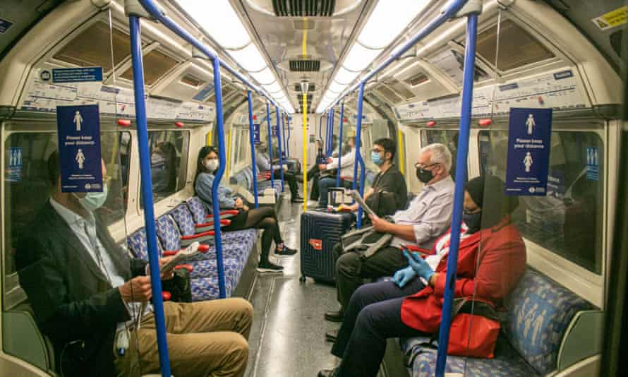 distanced passengers with masks on tube