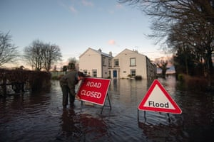 Gabrielle Burns-Smith erects a road closed sign on Warrington Lane on the outskirts of Lymm in Cheshire