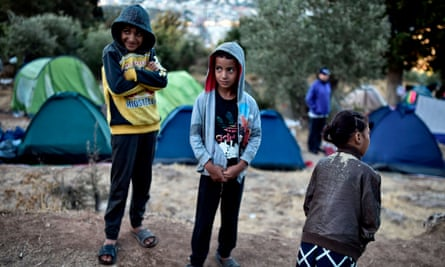 Children stand amid a makeshift tent camp near the overcrowded facility on Samos