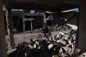 A Syrian man rides his bicycle past the rubble of destroyed buildings in the rebel-held town of Douma, Syria