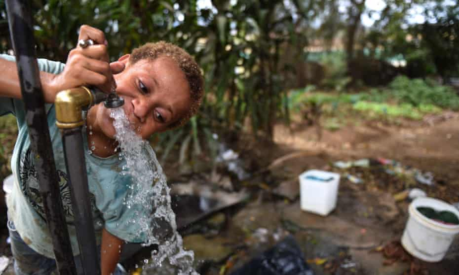A child drinks from an open-air tap