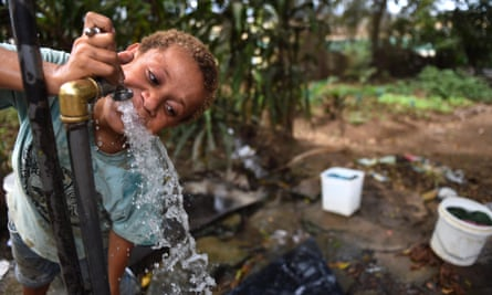 A child drinks water from the only tap for more than 100 people in a shanty town in the suburb of 9 Mile in Port Moresby, Papua New Guinea