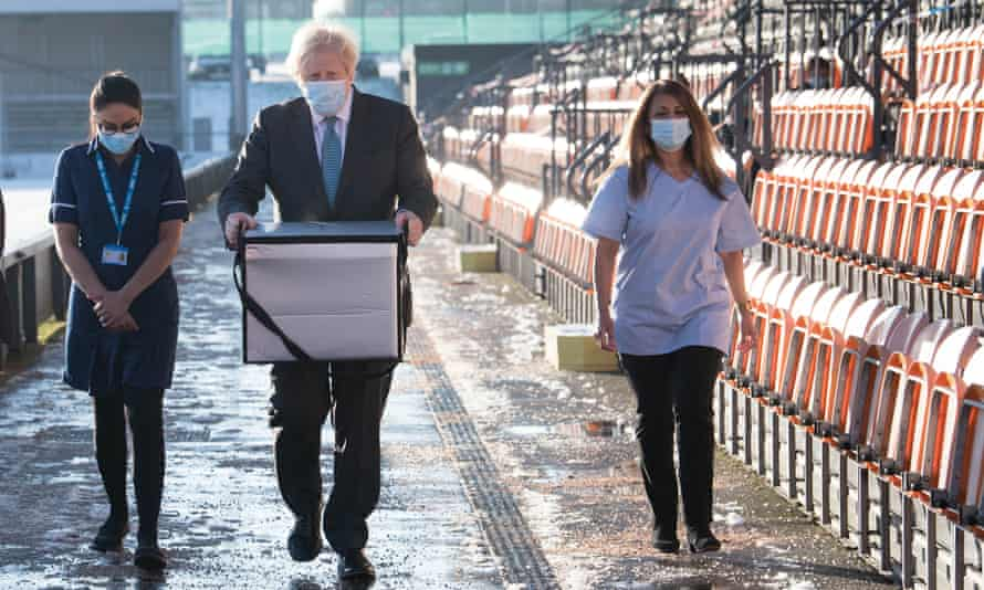 Boris Johnson carrying a bag of coronavirus vaccines at a vaccination centre in north London.