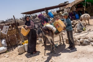 Awdeh's mother, daughter and nephew attach jerry cans to a donkey. Every day, family members deliver water to their relatives, who live scattered throughout the area.