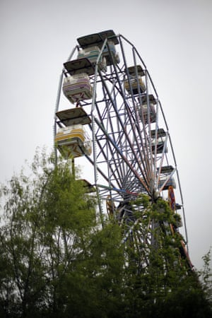 Overgrown trees almost obscure the ferris wheel