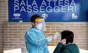 A medical worker checks the temperature of a passenger on arrival at a ferry port in the Sicilian city of Messina.