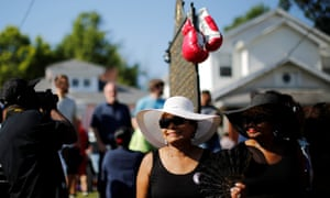 Boxing gloves are seen hanging on a historical marker outside Muhammad Ali's childhood home as mourners gather for the funeral procession Friday.