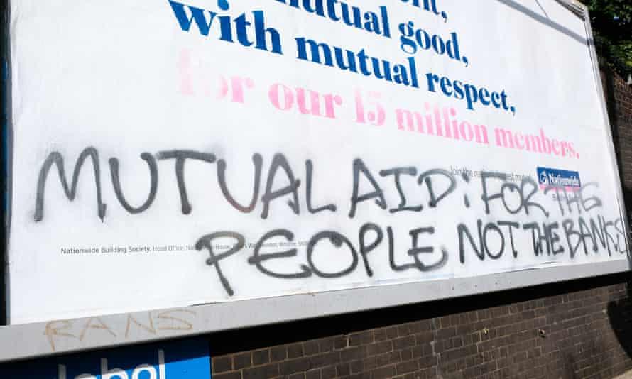 Mutual aid graffiti on bank billboard ad