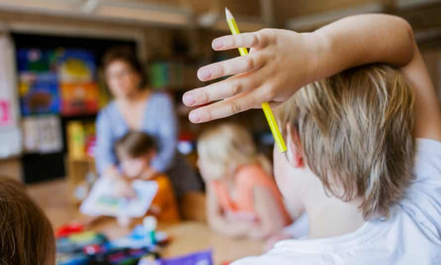 Rear view of boy with pencil raising hand in classroom