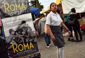 A student walks by a poster for Roma in Tlaxiaco