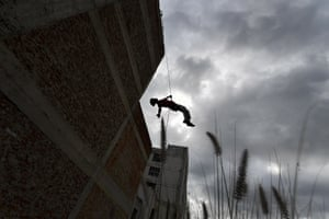 An acrobat of the Third Planet school practises rappel aerial dance from a building in downtown Caracas.