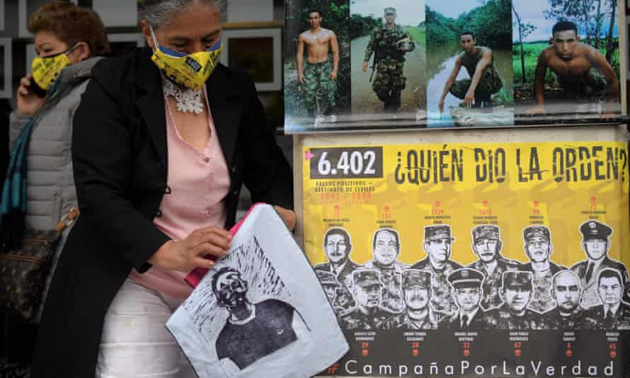 Members of the Mothers of False Positives (Mafapo) civil organization wear face masks as they stand next to a poster reading Who gave the order? during a protest outside the Special Jurisdiction of Peace (JEP) building in Bogotá, on Tuesday.