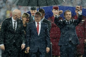 It takes so long for the trophy presentation to begin that it starts pouring down. Somehow Russian President Vladimir Putin is the only one with an umbrella.
