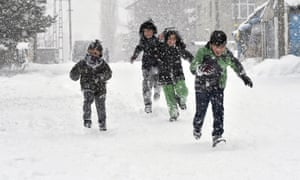 Children play in the snow in the city of Kars.