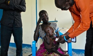 In a Unicef-supported feeding centre, 12-month-old Peter Ajus is weighed. His mother has walked for four days to bring him in.