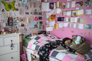 Girl lying on her bed, with pink walls