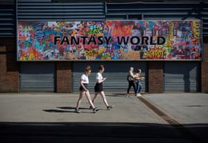 Girls walk past an amusement arcade hoarding in Cleethorpes, as hot weather descends upon the UK
