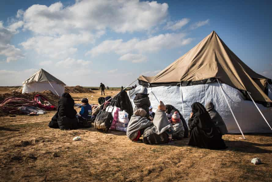 People who fled heavy fighting between the SDF and Isis in Baghuz sit in front of a tent inside a civilian screening point