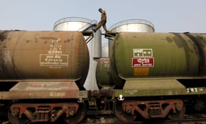 A worker walks along the top of an oil-tanker wagon to check the freight level on the outskirts of Kolkata