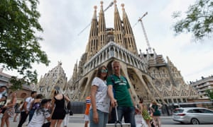 Tourists pose for selfies in front of the Sagrada Familia basilica in Barcelona in August